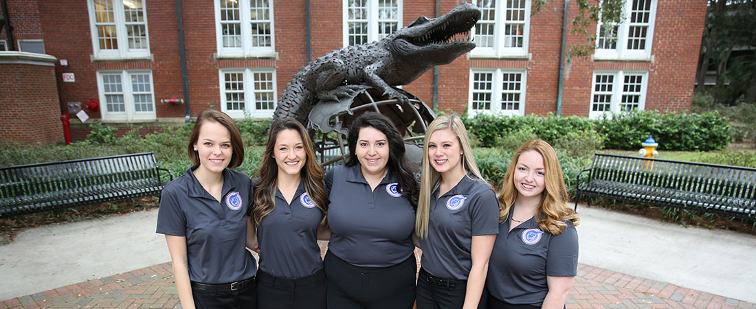 Group of females students in front of the Gator Ubiquity statue