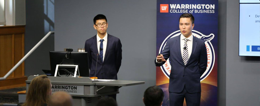 Two male students presenting at podium at the competition